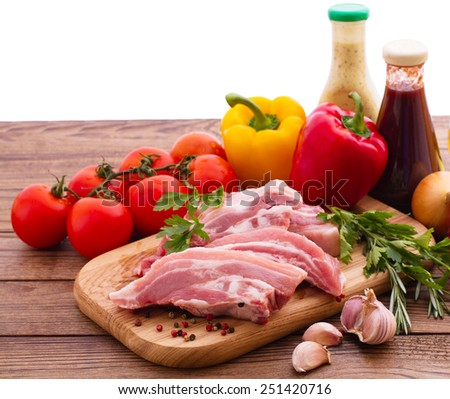 Sliced pieces of raw meat for barbecue with fresh vegetables and mushrooms on wooden surface.