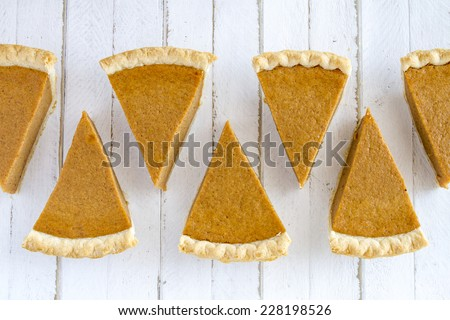 7 slices of homemade pumpkin pie in row sitting on white wooden table - stock photo