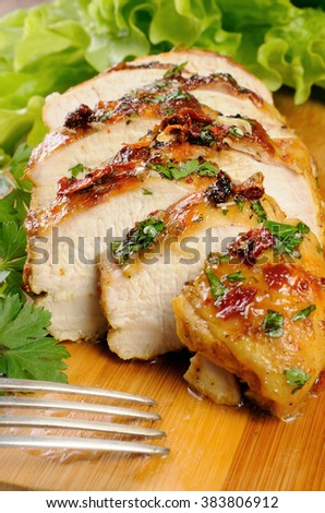 Slices of roasted chicken breast on a wooden board with fresh herbs
