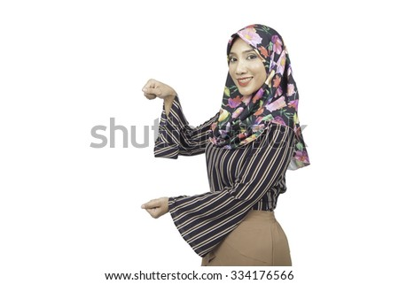 slim tanned female in muslimah fashion showing open hand palm with copy space for product or text, on a white background