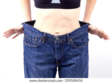 slim woman is showing how much weight she lost. wide blue jeans skinny girl. Diet weight loss concept - stock photo