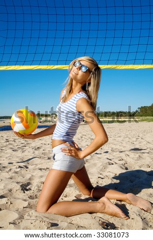 Slimness posture of the  beautiful girl with a ball on a beach - stock photo