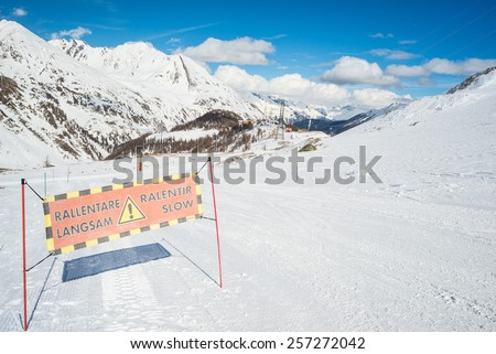 """Slow skiing"" warning sign on ski slope in ski resort with majestic panoramic view of the italian french Alps. - stock photo"