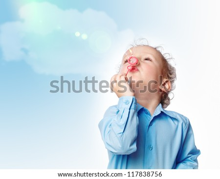 small boy blowing a bubble in the sky - stock photo