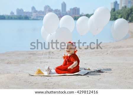 Small caucasian plays on river bank with white balloons. Portrait of cute adorable baby girl in red dress celebrating her first birthday on sunny sand beach with balloons looking into camera - stock photo