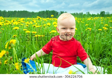 small child the baby  plays on a green meadow with dandelions - stock photo