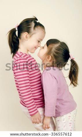 Small cute sisters playing together - stock photo