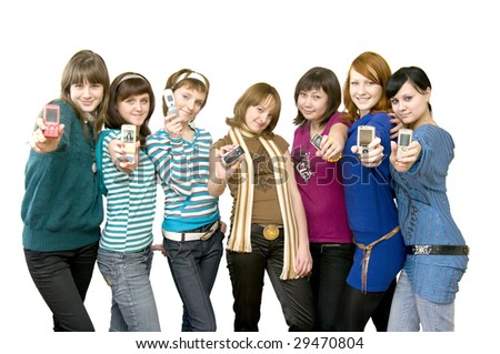 Small group of happy teenagers. Smiling and looking at camera. Holding and showing mobile phones. White background - stock photo