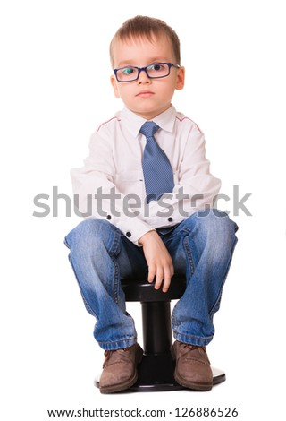 Small sad boy in glasses, shirt and jeans sitting on the black chair. Isolated on white background. - stock photo