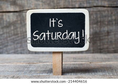 Small wooden framed blackboard on wooden background with text It's Saturday - stock photo