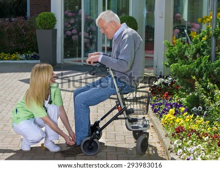 Smiling Blond Nurse Helping Senior Man with Walker to Tie Shoe Laces Outdoors in front of Retirement Building on Sunny Day near Garden. - stock photo