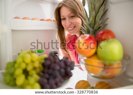 Smiling woman look at grape and apple in refrigerator - stock photo