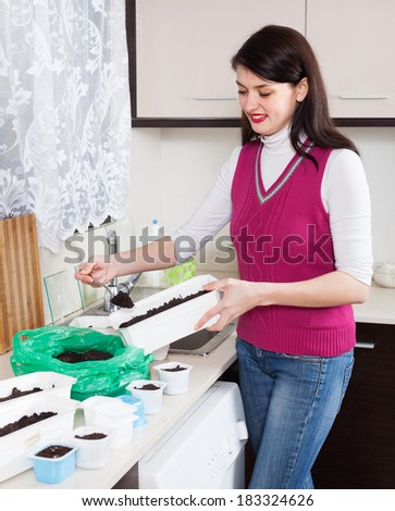 Smiling woman making  ground for seedlings at home kitchen