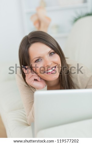 smiling woman using her laptop lying on the sofa in the living room