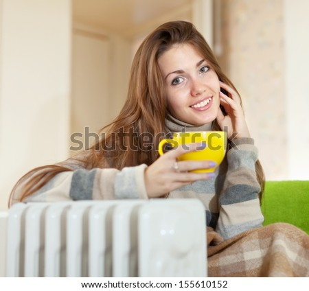 smiling woman  with yellow cup near oil heater at home - stock photo