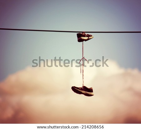sneakers hanging from electrical wire against a blue sky with clouds toned with a retro vintage instagram filter effect  - stock photo
