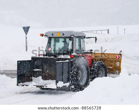 snowplow tractor cleaning a road in winter time