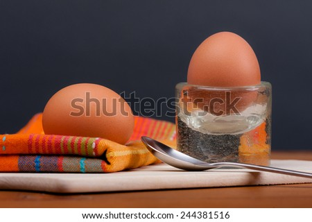 2 soft-boiled eggs on a wooden board. With a dark-grey background.  - stock photo