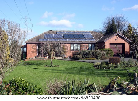 16 Solar Panels on Bungalow Roof in UK - stock photo