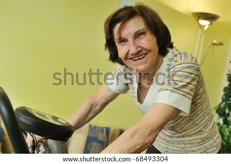 80 something mature woman exercises on spinning bicycle at home - stock photo
