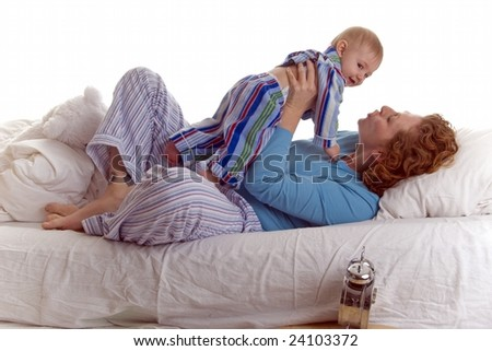 30 something Mom and baby sharing a bonding moment in bed - stock photo