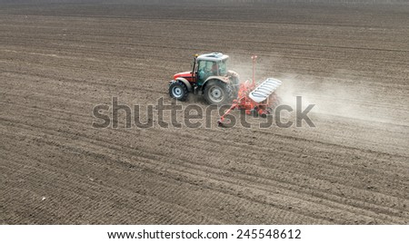 sowing crops at field with sowing machine - stock photo