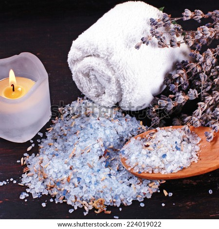 spa composition with natural lavender bath salt, candle and dry lavender on dark wood background - stock photo