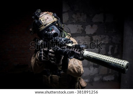 Special forces soldier wearing helmet and mask holding rifle with silencer aiming at camera.Selective focus/Special Forces soldier in protective uniform aimingg from rifle - stock photo
