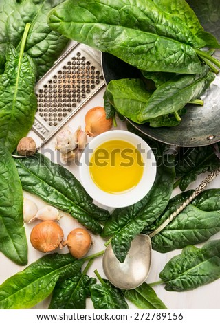spinach cooking ingredients: onion,oil, nutmeg and garlic, top view, close up - stock photo
