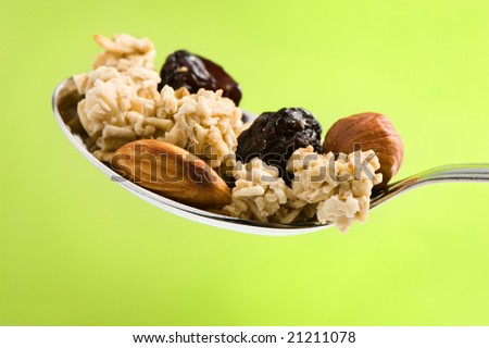spoon with health food : cereal, nuts and raisins. Green background. - stock photo