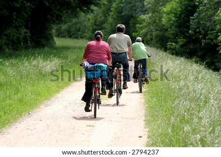 """Sports family walking in bicycle in full nature"""