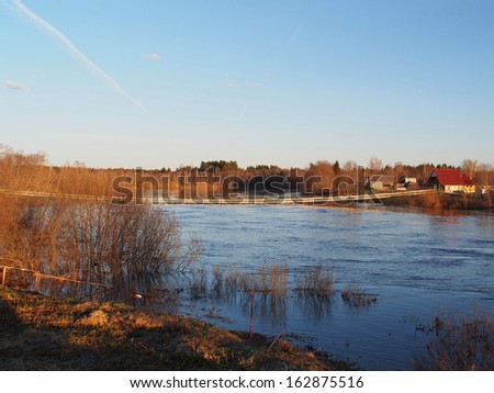 Spring rural landscape. High water, spring flood of the river and the flooded wood. River Msta, Novgorod region, Russia