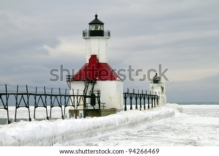 """St. Joseph Winter"" -- Ice forms on Lake Michigan and the pier of the Lighthouse at St. Joseph, Michigan. - stock photo"