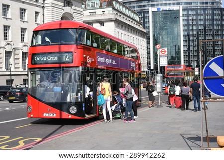 21st June 2015: London, UK, People at St Thomas Hospital Bus Stop in London, station is next to Big Ben, Iconic red color buses at bus stop. - stock photo