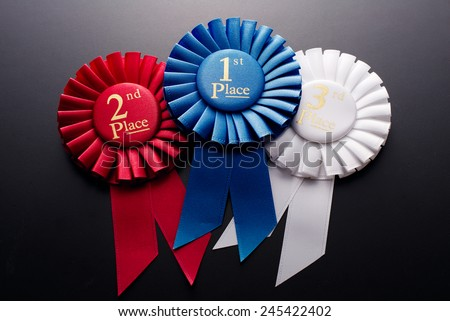 1st, 2nd and 3rd place pleated ribbon rosette on a dark background - stock photo