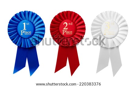 1st, 2nd and 3rd Place pleated ribbon rosettes or badges in blue, red and white respectively with central text isolated in a row on a white background, overhead view - stock photo