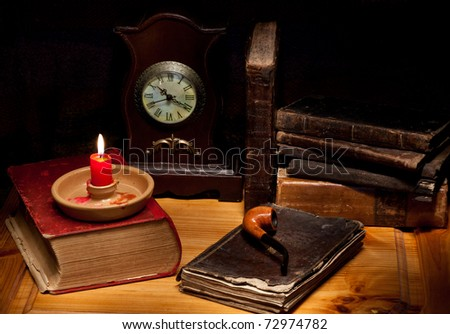 still life with old books, clock, candle and pipe - stock photo
