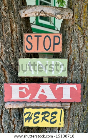 """Stop and eat here"" sign on tree trunk"