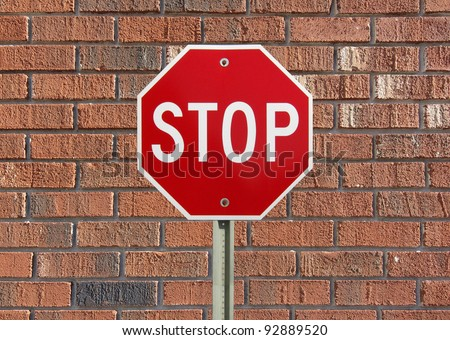 Stop sign up against a brick wall - stock photo