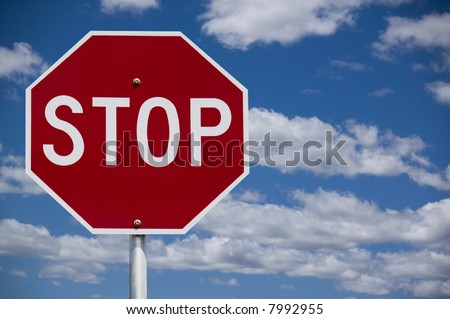 """Stop"" street warning sign against a blue sky background"
