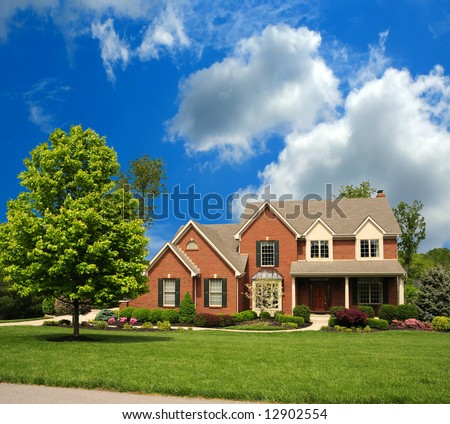 2-Story Brick Suburban Home on a sunny summer day. - stock photo