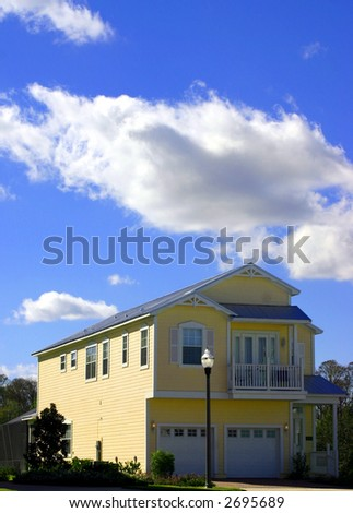 2-story yellow american dream home against perfect blue sky and garage - stock photo