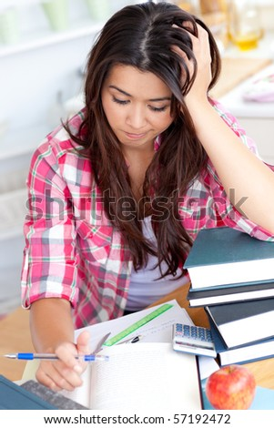 Stressed student doing her homework sitting at the desk - stock photo