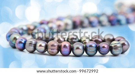 String of pearls over  with blue lights in the background - stock photo
