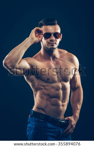 strong athletic man  in sunglasses on black background. To pump the abdominals. - stock photo