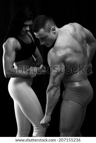 Strong man and a woman posing  - stock photo