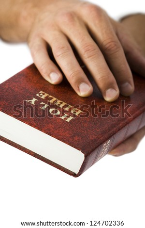 Studio shot of hands holding Bible