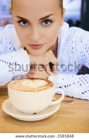 stunningly beautiful blue eyed young woman with a hot drink shallow DOF - stock photo