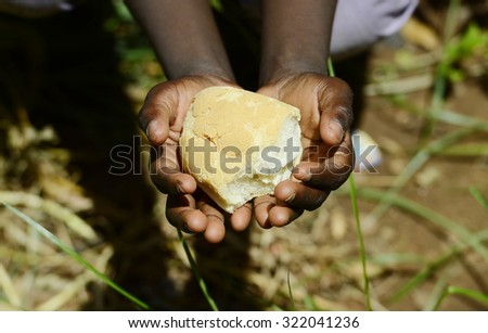 Stunting African Children Symbol - Baby Girl Holding Bread Malnutrition. Starving Hunger Symbol. Black African girl holding bread as a malnutrition symbol.  - stock photo