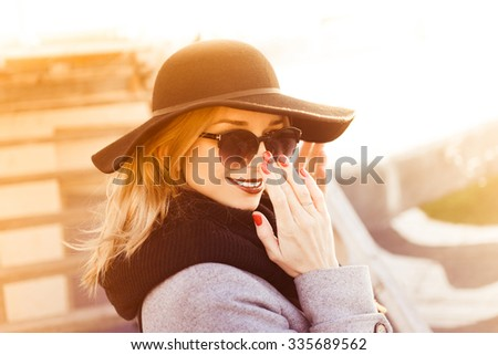 Stylish young beautiful blonde girl on a sunny day in an elegant black hat with sunglasses with full red lips smiling posing at sunset close-up on a city street Happy Life Style autumn - stock photo